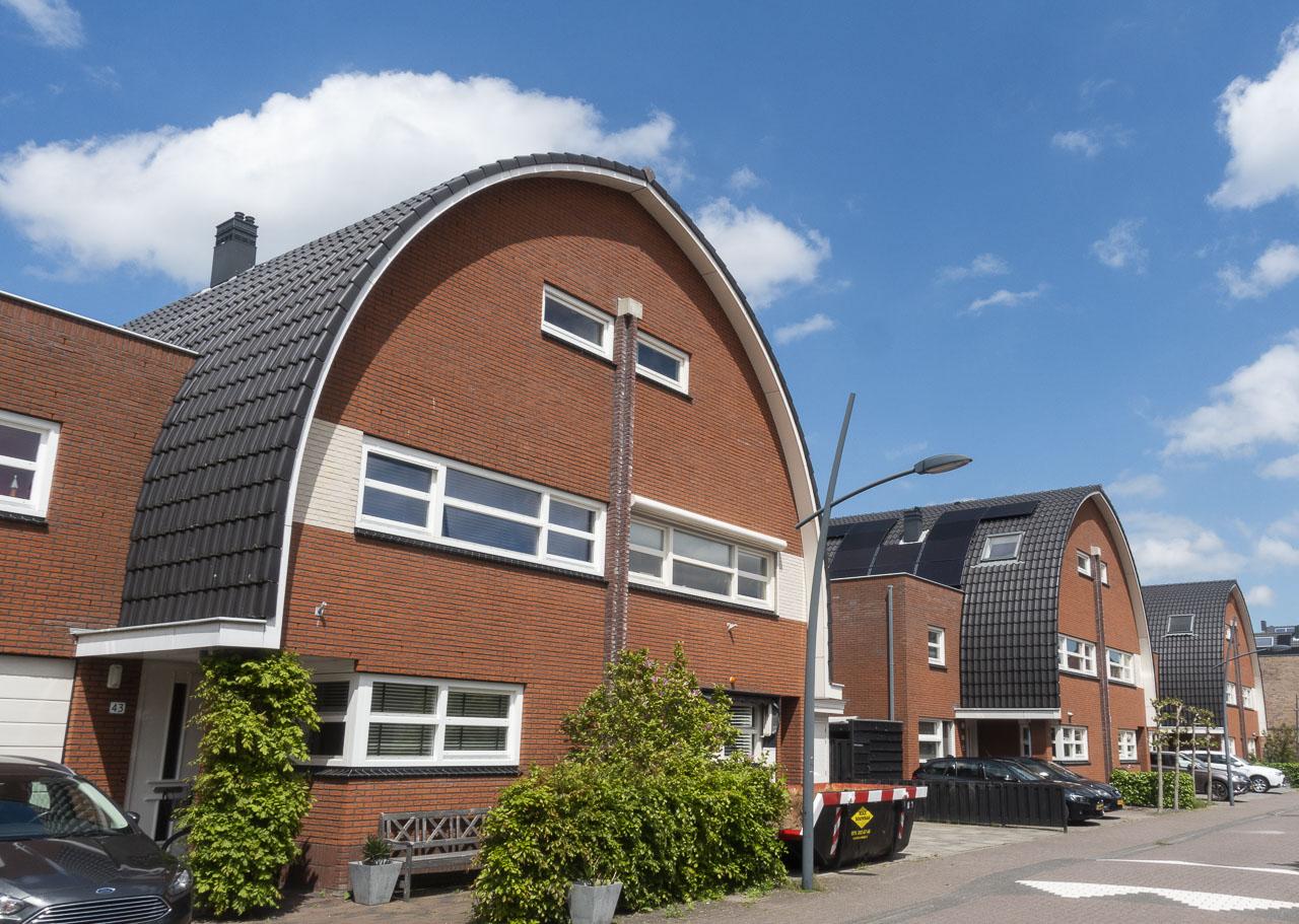 De grotere typen huizen met spitsbooggevels. W.M. Dudokstraat.